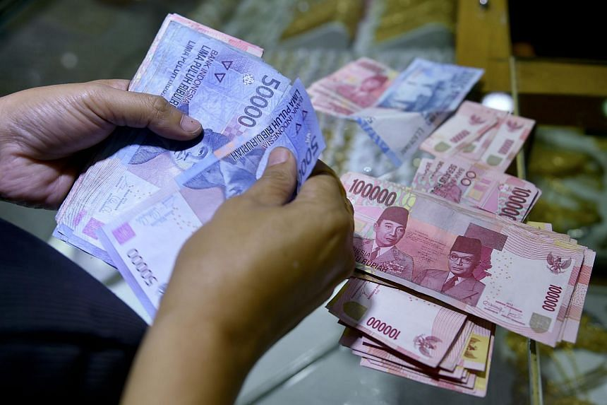 A customer counting Indonesian rupiah banknotes at a shop in Jakarta on Aug 25, 2015.