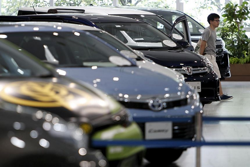 A visitor walking past Toyota Motor's cars displayed at the company's showroom in Tokyo, Japan.