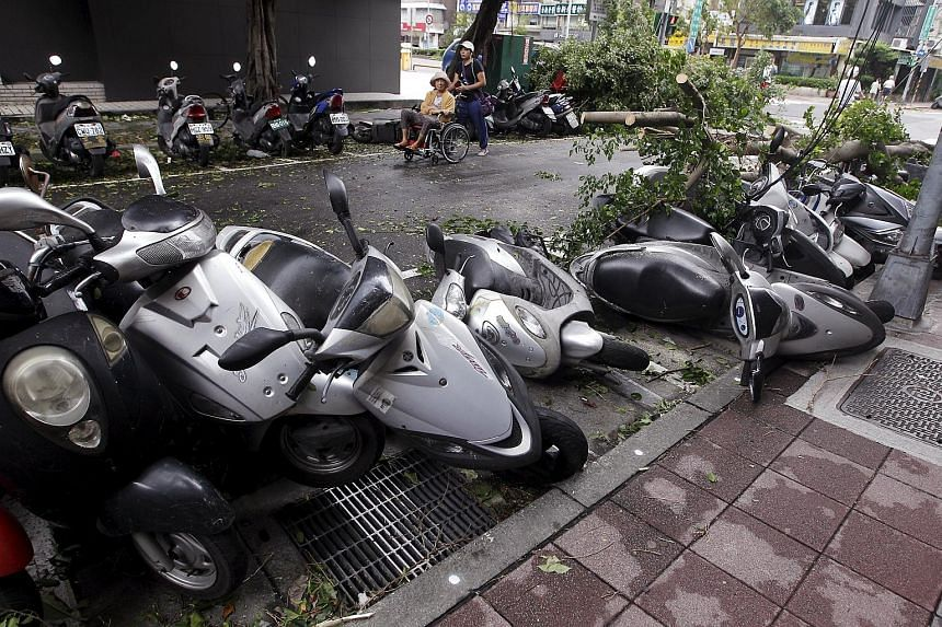 People walking past uprooted trees and damaged motorcycles, in the aftermath of Typhoon Dujuan in Taipei, Taiwan, on Sept 29, 2015.