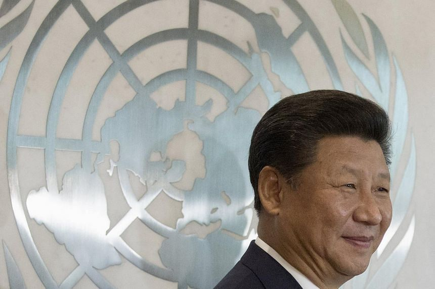 Chinese President Xi Jinping stands in front of the United Nations emblem.