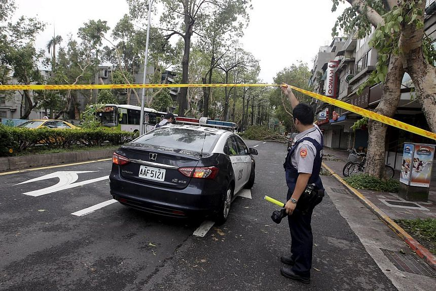 A police officer cordoning off a road, which is blocked by uprooted trees, in the aftermath of Typhoon Dujuan in Taipei, Taiwan, on Sept 29, 2015.