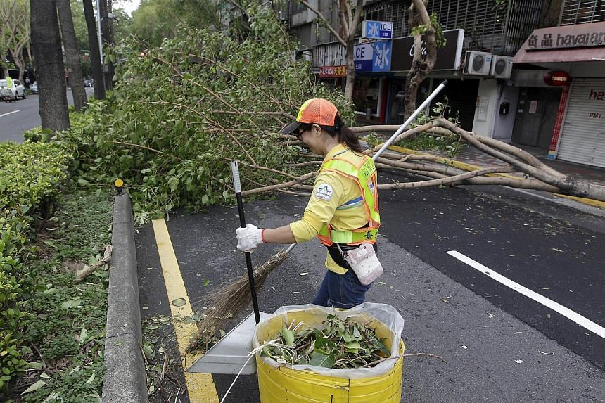 A worker removing trees uprooted by strong winds from Typhoon Dujuan in Taipei, Taiwan, on Sept 29, 2015.