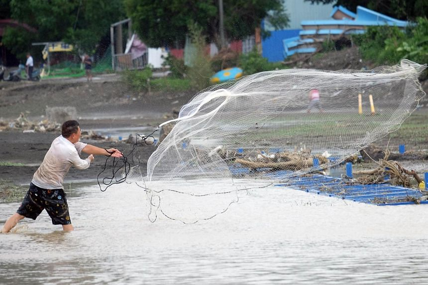 A local resident casting his net from the Xindian river after Typhoon Dujuan passed in the New Taipei City on Sept 29, 2015.