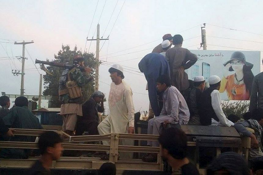 Taleban fighters and residents are seen on top of a military vehicle in Kunduz, a day after the Taleban took control of the city, on Sept 29, 2015.