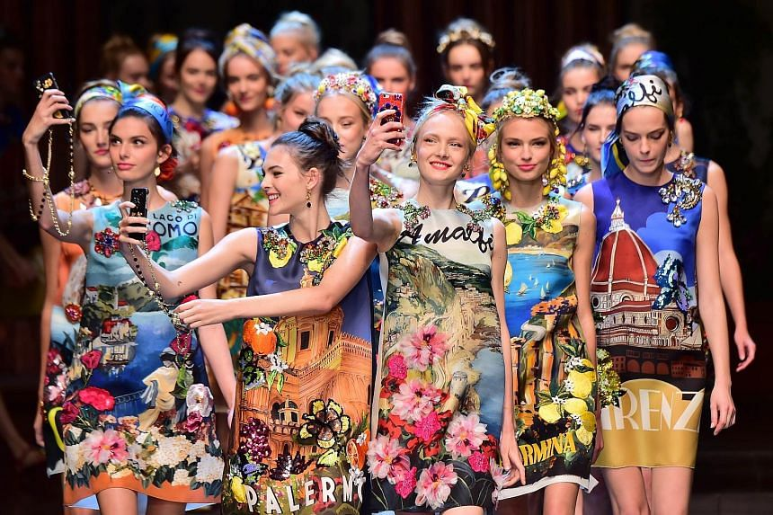 Models take selfies during the show for fashion house Dolce & Gabbana at Milan Fashion Week on Sunday.