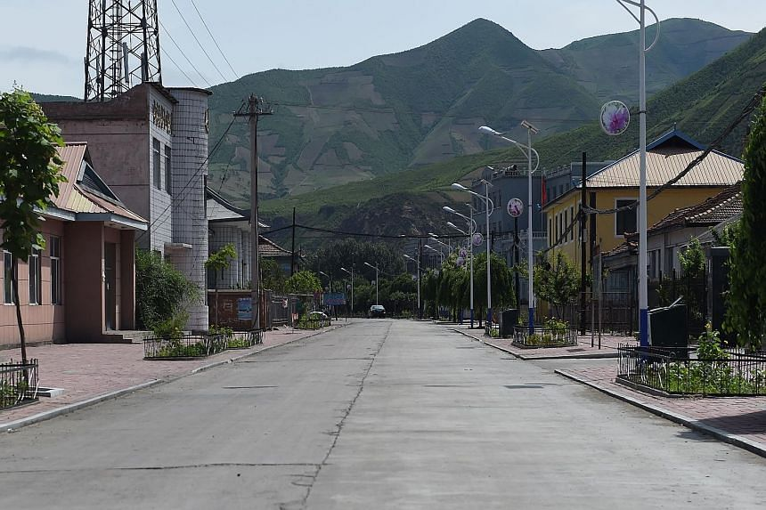A deserted street in the Chinese border village of Nanping, with the hills of North Korea behind. After a spate of murders - allegedly by frontier-crossing intruders - frightened villagers are keen to leave.