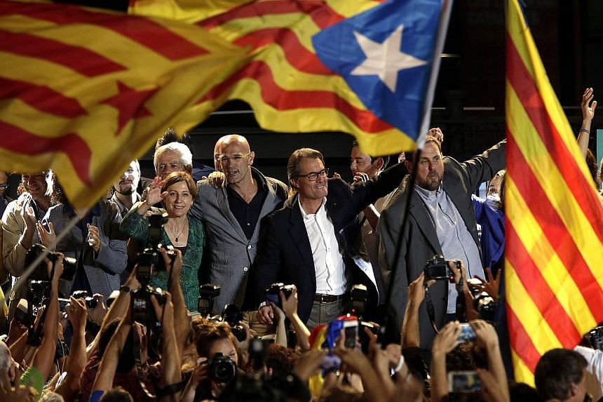 Pro-sovereignty party Junts pel Si (Together For Yes) leaders Raul Romeva (centre), Artur Mas (second from right) and Oriol Junqueras (right) celebrating in Barcelona, Catalonia's capital, after separatist groups won the majority of seats in the regi