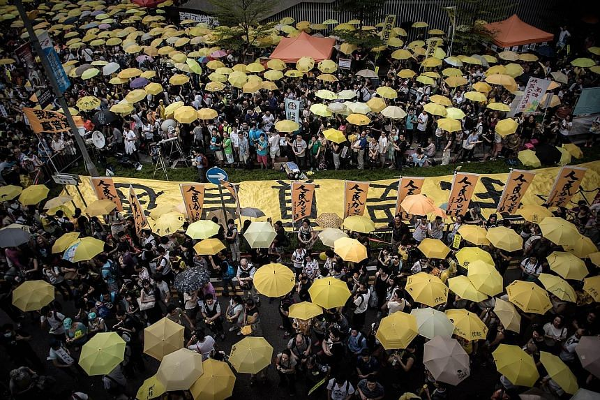 Armed with trademark yellow umbrellas, activists gathered outside Hong Kong's government headquarters yesterday to mark a year since the start of the Occupy movement that tried to force Beijing to liberalise rules on the election of the city's leader
