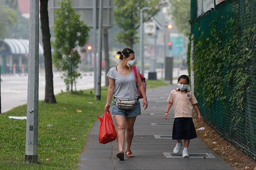 A woman and child heading home in Pasir Ris Drive 6 at 3.30pm yesterday. Most schools have minimised their outdoor activities. Heavy rain and haze at about 6pm yesterday at Jubilee Bridge in southern Singapore. For most of the school day yesterday, t
