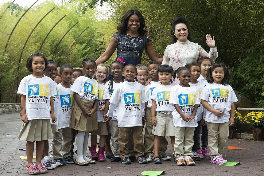 US First Lady Michelle Obama and China's First Lady Peng Liyuan with students from Washington Yu Ying Public Charter School after their performance at the Smithsonian's National Zoo last Friday in Washington, DC. Due to a projected faster rise in the
