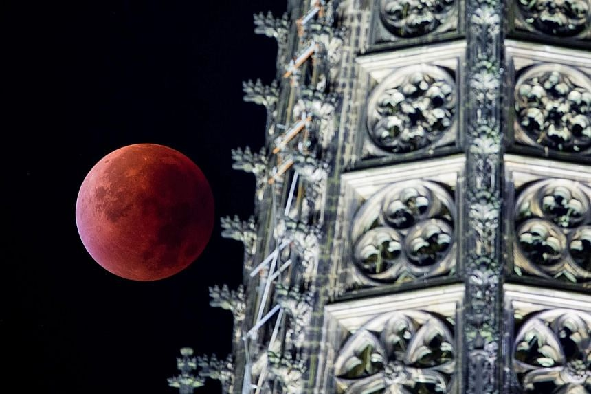 The supermoon (top) appearing above Cologne cathedral in Germany yesterday. (Above) In Cape Town, South Africa, Earth's shadow can be seen partially covering the Moon.