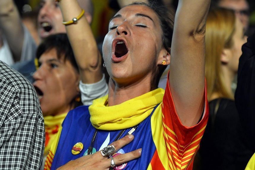 A woman sporting a pro-independence T-shirt chanting slogans following the closing of polling stations during the Catalan regional election on Sunday in Barcelona.