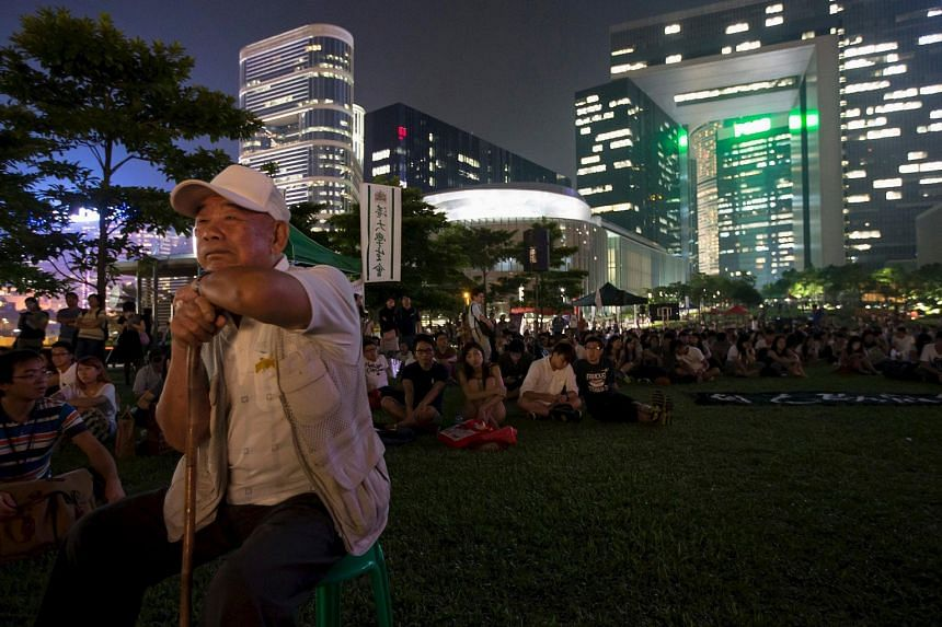 """""""Uncle"""" Wong, 90, at the pro-democracy rally on Sept 24 last year (top) and posing in the spot last Wednesday (above)."""