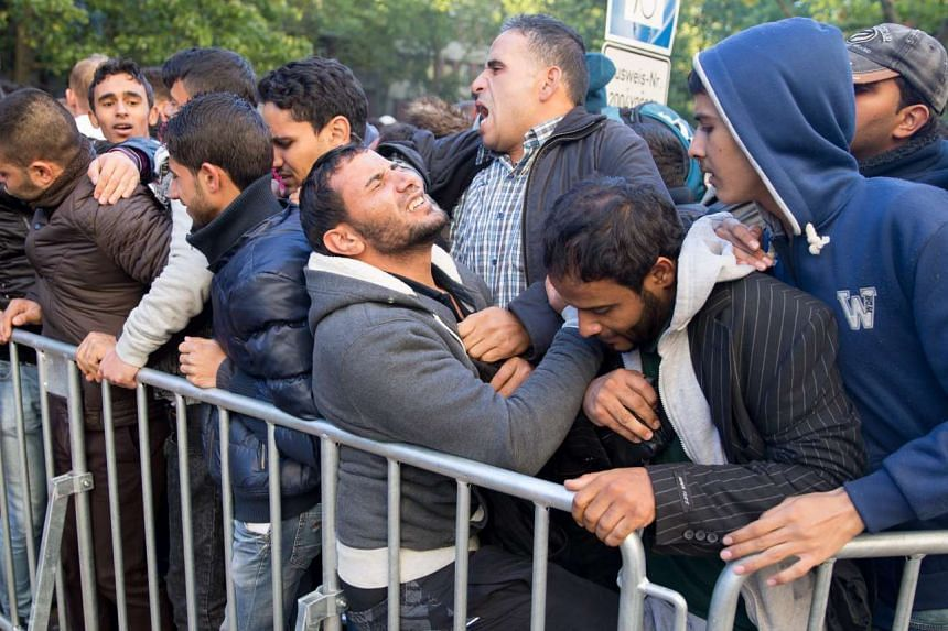 Refugees jostle as they wait to be registered and provided with accommodation, outside the State Office for Health and Social Issues in Berlin, Germany.