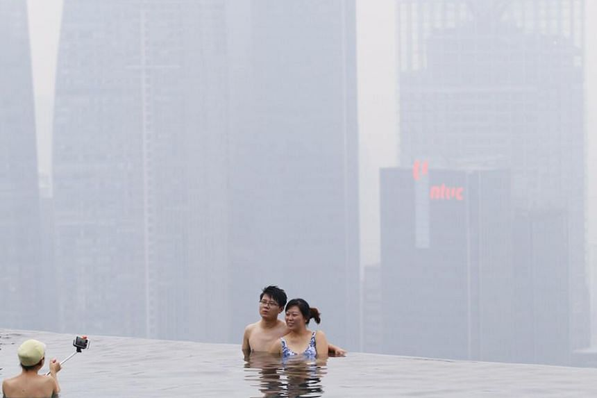 Singapore's financial district is obscured by haze as seen from the infinity pool on the top of Marina Bay Sands at around 7.20pm on Sept 29, 2015.