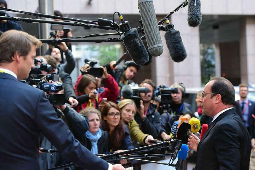 Journalists crowd France's President Francois Hollande as he arrives to attend an European Union (EU) emergency summit on the migration crisis.