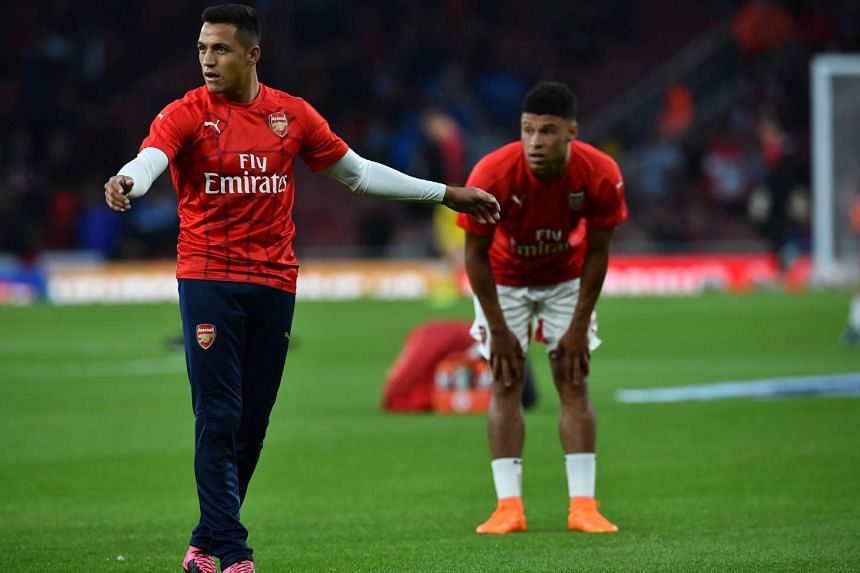 Arsenal striker Alexis Sanchez (left) and midfielder Alex Oxlade-Chamberlain warm up before their English Premier League football match against Liverpool at the Emirates stadium in London on Aug 24, 2015.