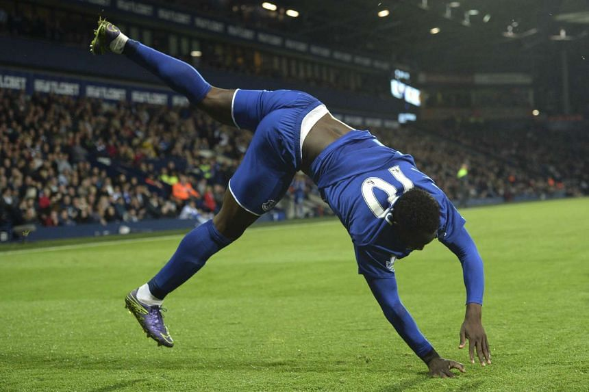 Everton's Belgian striker Romelu Lukaku does a flip and somersault as he celebrates scoring Everton's third goal during the English Premier League football match against West Bromwich Albion on Monday.