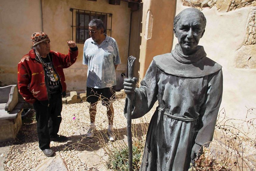 Chief Tony Cerda (left) of the Costanoan Rumsen Carmel Tribe of the Ohlone Nation and Rudy Rosales, Tribal Chairperson of the Ohlone Costanoan Esselen Natio, stand next to a statue of Franciscan Friar Junipero Serra at the Carmel Mission in Carmel, C