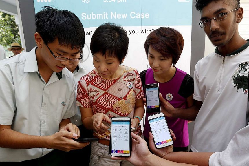 Then Minister in the Prime Minister's Office Grace Fu (second from left and South West District Mayor Low Yen Ling at the launch of OneService on Jan 25, 2015, together with students Wang Hao Ming (left) and Mogan Santhan (right).