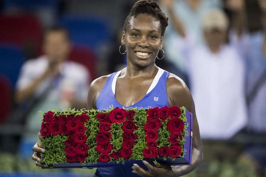 Venus Williams of the US celebrates her 700th career win after beating Julia Goerges of Germany in their women's singles match on day two of the Wuhan Open tennis tournament in Wuhan, China's Hubei province on Sept 29, 2015.