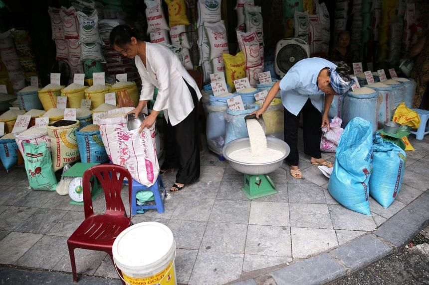 Women sell rice at their streetside stalls in Hanoi, Vietnam. A strong performance by export-orientated manufacturing and the service sector means the country looks set to beat official projections.