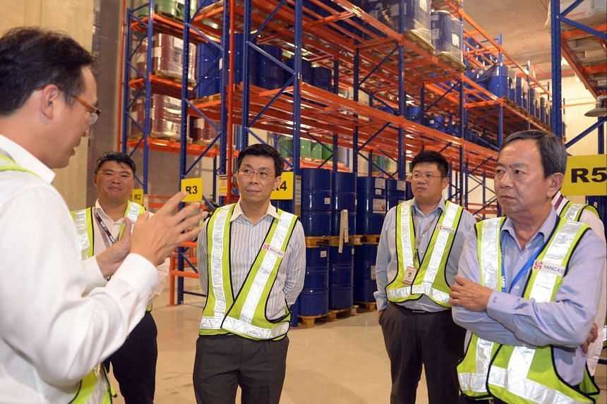 At Yang Kee Logistics, business operations general manager Mr Ong Swee Keong (far left) gives a site tour to Senior Minister of State for Trade and Industry and National Development Lee Yi Shyan (centre), accompanied by Mr Ken Koh, Yang Kee managing