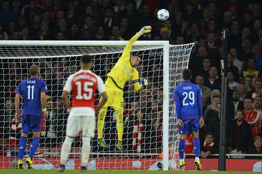 Olympiakos's Spanish goalkeeper Roberto Jimenez (second right) reaches high to tip a ball over the bar to make a save during the UEFA Champions League Group F football match between Arsenal and Olympiakos at The Emirates Stadium in north London on Se