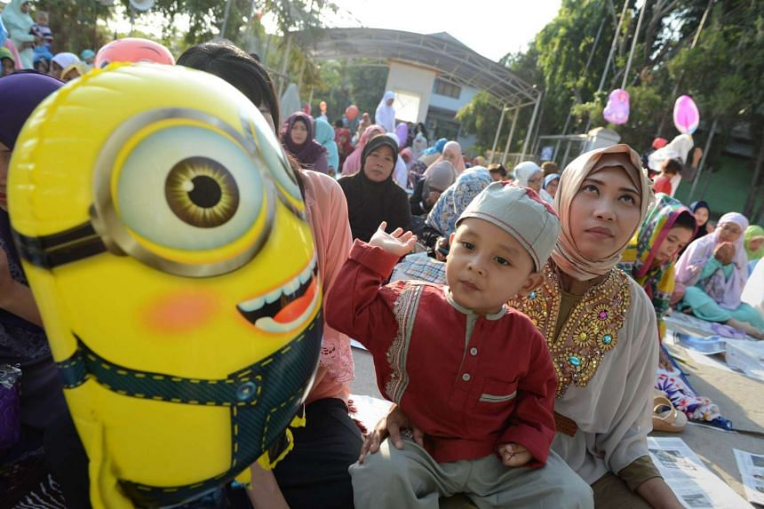 An Indonesian mother prays while her son plays with a balloon during morning prayers at a mosque in Jakarta on July 17, 2015.