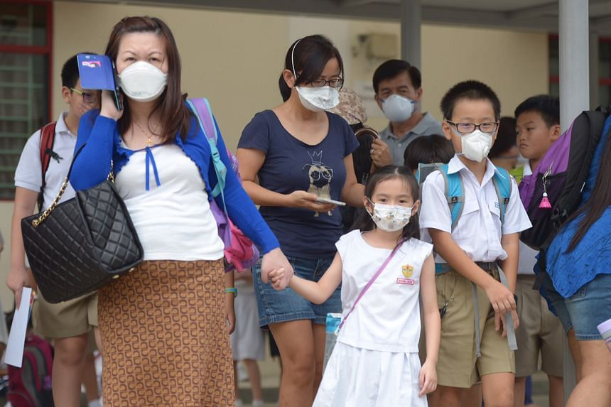 Students taking precautionary measures by wearing masks as hazy skies returned after a temporary respite over the weekend, as schools across Singapore reopened on Sept 28, 2015.
