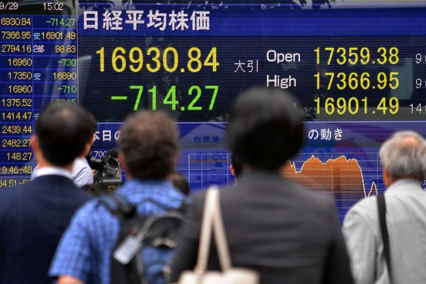 Pedestrians walking in front of a share prices board in Tokyo on Sept 29, 2015.