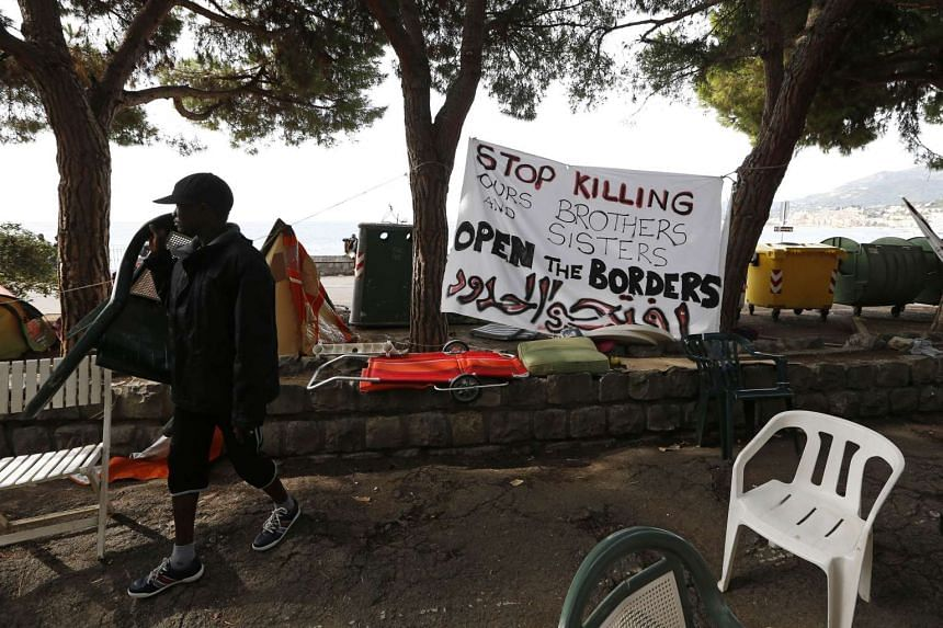 A man walking past a banner in a migrant and refugee encampment in Ventimiglia on the Italian-French border on Sept 15, 2015.