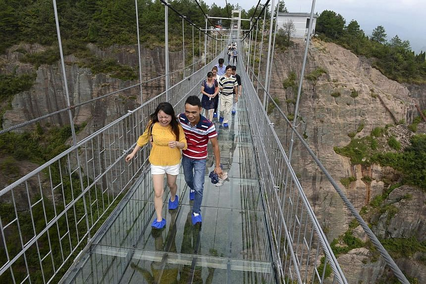 An aerial view of the 300m-long glass suspension bridge (above) at the Shiniuzhai National Geo-park in Hunan province, which opened to tourists (below) for the first time last Thursday.