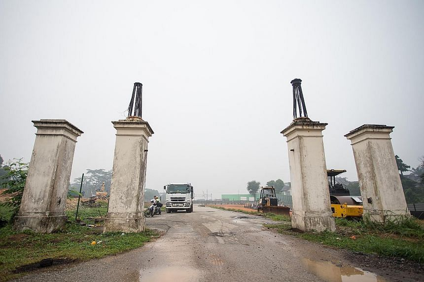 The cast iron gates (above) and four concrete columns (right) at the entrance of Bukit Brown Cemetery are making way for an eight-lane road.