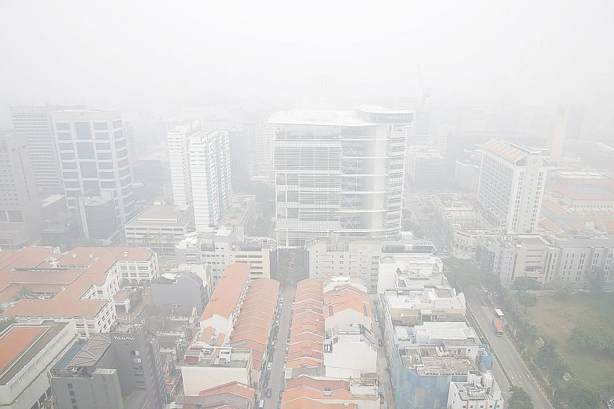 The National Library Building (centre) and the surrounding area blanketed in haze at around 1pm yesterday. The 24-hour PSI reading then was 167-213. Experts said that while rain can remove some of the airborne particles from the air, it cannot do the