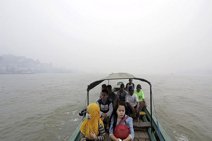 Residents crossing the haze-shrouded Musi River in Palembang, South Sumatra province, yesterday. Indonesia's Coordinating Minister for Political, Legal and Security Affairs Luhut Panjaitan and Defence Minister Ryamizard Ryacudu gave the assurance tha