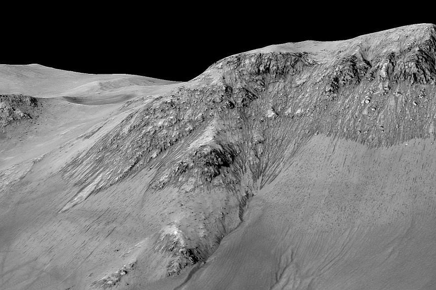A handout image, made available by Nasa on Sept 27, shows dark, narrow, 100m- long streaks flowing downhill on Mars. Scientists detected hydrated salts on these slopes at Horowitz crater, corroborating their original hypothesis that the streaks are f