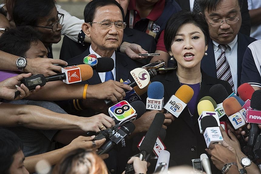 Yingluck Shinawatra, along with her brother-in-law Somchai Wongsawat, speaking to reporters at the court yesterday.