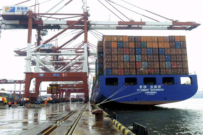 A cargo ship waits to be loaded with shipping containers at a port in Qingdao, Shandong province, China, on Sept 1, 2015.