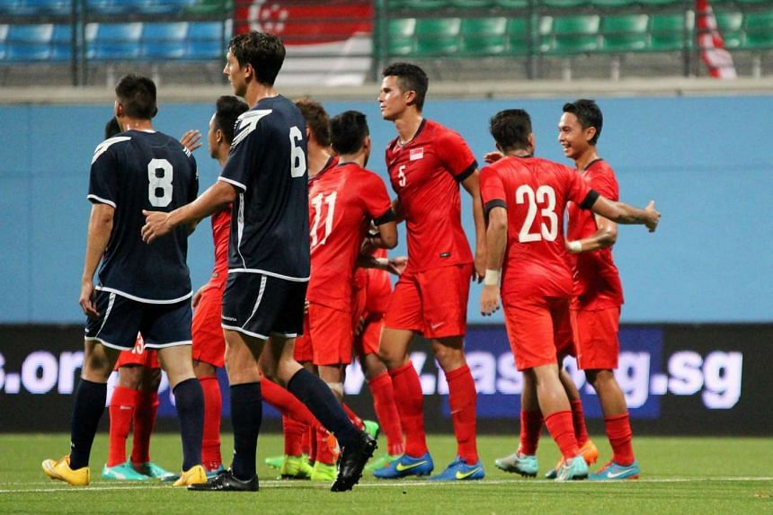 Singapore football players (in red) during a friendly international against Guam held at the Jalan Besar Stadium on Mar 31, 2015.