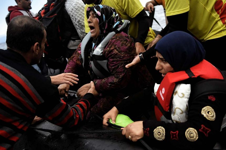 Women reacting as they arrive on a dinghy with other refugees and migrants to the Greek island of Lesbos on Sept 29, 2015.