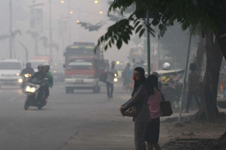 Indonesian motorists and pedestrians travelling under a blanket of haze in Palembang, Sumatra on Sept 29, 2015.