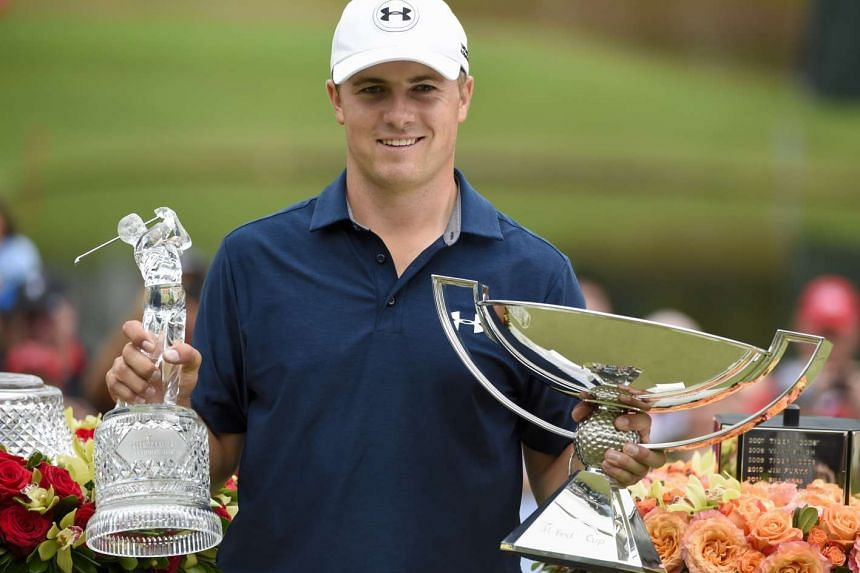 Jordan Spieth holds up his trophies after winning the final round of the Tour Championship by Coca-Cola at East Lake Golf Club.
