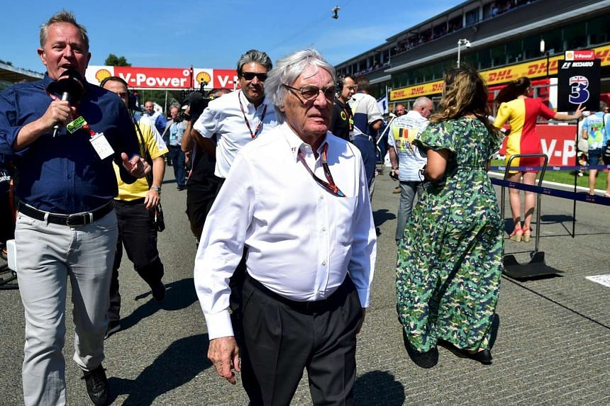 Formula One supremo Bernie Ecclestone (center) walks on the starting grid before the start of the Belgian F1 Grand Prix in Spa-Francorchamps, Belgium, Aug 23, 2015.