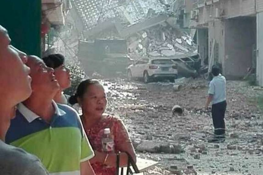 People look on after explosions hit Liucheng county, Guangxi Zhuang Autonomous Region, China, Sept 30, 2015.