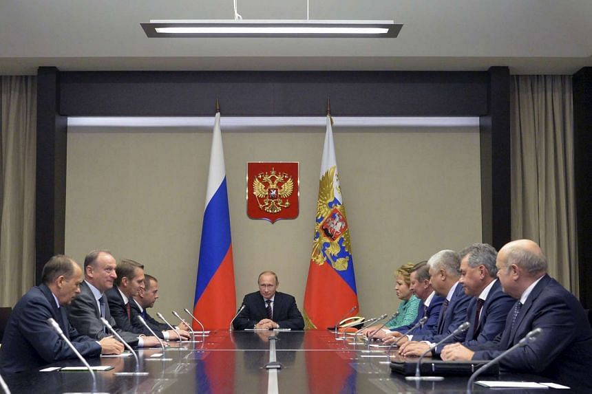 Russian President Vladimir Putin (center) chairs a meeting with members of the Security Council at the Novo-Ogaryovo state residence outside Moscow, Russia, Sept 29, 2015.  Putin on Wednesday won permission from parliament to carry out air strikes in