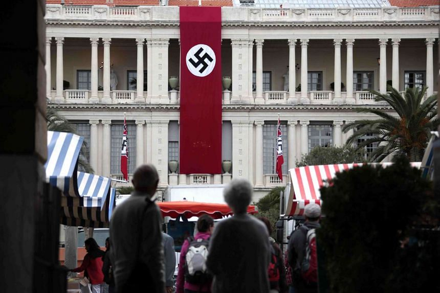 A Nazi swastika banner hangs on the facade of the Prefecture Palace in Nice which is being used as part of a movie set during the filming of a WWII film in the old city in France on Tuesday.