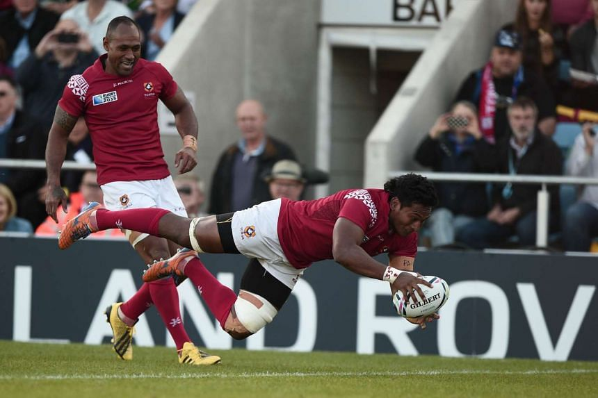 Tonga's back row forward Jack Ram dives over the line to score their fourth try during the Pool C match of the 2015 Rugby World Cup between Tonga and Namibia on Tuesday.