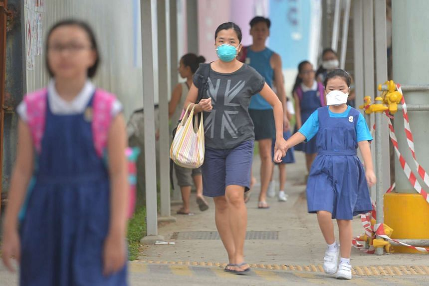 Pupils of CHIJ Toa Payoh wearing masks heading to school at 7.30am on Oct 1, 2015.