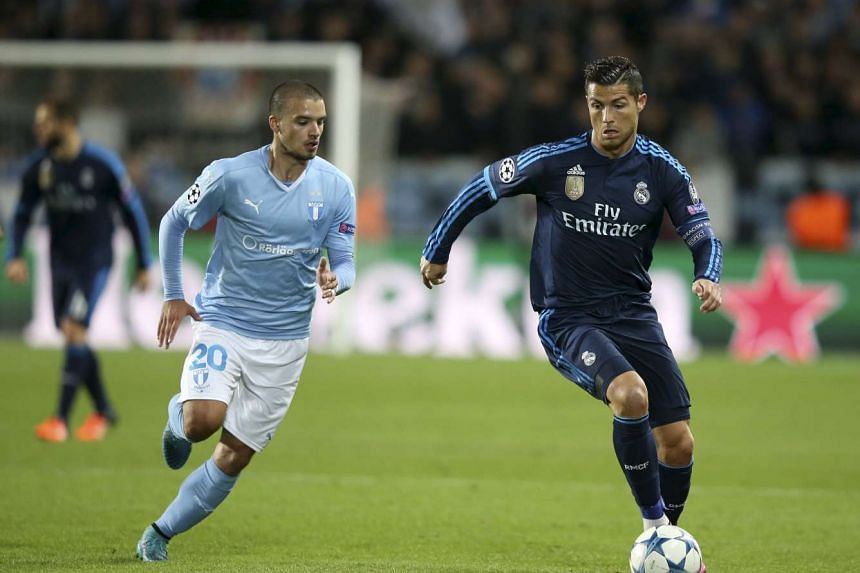 Malmo FF's Vladimir Rodic (left) challenges Real Madrid's Cristiano Ronaldo during their Champions League group A soccer match at Malmo New Stadium in Malmo, Sweden on Sept 30, 201